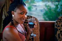 Black woman traveling in the Livingstone Express luxury train drinking wine. The Royal Livingstone Express offers the discerning guests the ultimate fine dining experience going back in time to the age of steam train travel. Luxury steam train dining as you travel on the historic Mulobezi Railway line, formerly one of the largest private rail networks in the world. The train itself consists of 5 carriages restored by Rohan Vos of Rovos Rail and pulled by either Locomotive 156 or Locomotive 204 and is fully air conditioned. Fulfil your romantic fantasy, escape on a late afternoon train journey amidst the untamed natural Zambia bushveld. Sun International is proud to announce the inauguration of the Royal Livingstone Express, a joint venture between Sun International and Bushtracks Africa.