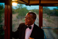 One of the railway workers of the Livingstone Express luxury train. Fine dining is redefined when the venue is the dining car of a 1920's steam train, in the middle of the Zambian bushveld. The Royal Livingstone Express is a joint venture between Bushtracks Africa and Sun International. This unique dining experience is fully inclusive and guests are transferred from all over Livingstone and the surrounding lodges to the old Mulobezi Line Offices in Livingstone town. Walking up to the train on a red carpet sets the mood for this must-do experience. Each guest is personally greeted and offered a welcome-drink as they board the immaculate vintage first-class Lounge carriage. The Royal Livingstone Express consists of five carriages, restored by Rohan Vos of Rovos Rail and these include two dining cars, a club/kitchen car, lounge car, and an observation car and is pulled by either a 10th class No. 156 or a 12th class No. 204 locomotive. Once all guests are aboard the journey commences through Dambwa suburb towards the Mosi-oa-Tunya National Park, running parallel to the Zambezi River.