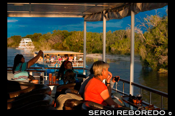 "Cruise along the Victoria Falls aboard the "" African Queen"".  Sunset cruises on the Zambezi River at Victoria falls watch hippo pods & elephants sometimes crossing the Zambezi. Guests are collected from their hotel or lodge at 15:30 in winter and 16:00 hrs in the summer months and transferred to the jetty site. Cruise departures at 16:00 hrs in winter and 16:30 in summer. Following this sunset cruise, you will be transferred back to your hotel between 18:30 hrs and 19:00 hrs (winter and summer respectively). At the jetty side guests are met by a Traditional African Band before signing the standard Indemnity Form. After a safety briefing and talk guests board the safari boat. Heading off downstream, meandering through the islands, the guides will talk to you and describe the flora and fauna as well as the prolific bird life and wildlife. Bird enthusiasts will be rewarded by sightings such as the African Finfoot, Open-billed Storks, Yellow-billed Storks and Sacred Ibis. The cruise is conducted at a slow pace for you to enjoy the relaxed ambience and the beauty of the mighty Zambezi river. Snacks and drinks are available during the trip. The Zambezi River Safari lasts about 2 hours. At the end of the safari guests are transferred back to their hotel/lodge."