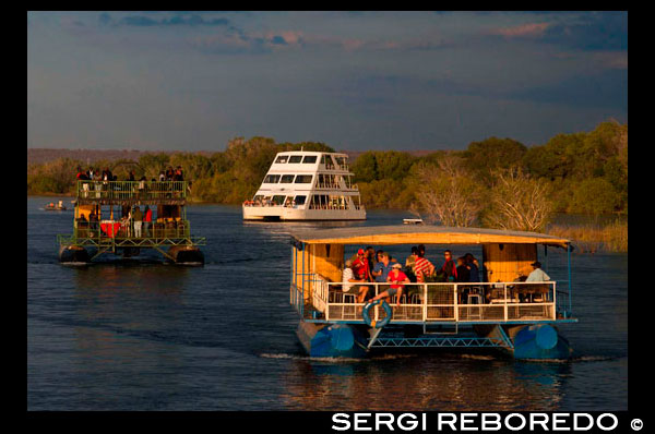 "Cruise along the Victoria Falls aboard the "" African Queen"".  Other boats sailing in the Zambezi River. Take a Sunset Cruise down the mighty Zambezi River. This Sundowner Cruise takes you down the Zambezi River for a beautiful journey!. The Zambezi Sunset River cruise is a superb way to relax and enjoy the beauty of the River. You may have the opportunity to see a variety of game; including hippo, crocodile, elephant and sometimes even rhino in their home environment, as well as enjoy the many different bird species. The Sunset cruise is very popular and includes finger snacks, beer, wine, champagne and soft drinks. There are great photo opportunities against often-spectacular African sunsets. The cruise lasts for approximately 2 hours."
