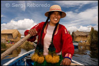Peruvian Altiplano. A woman dressed in regional costumes sails his boat between the islands of the Uros.