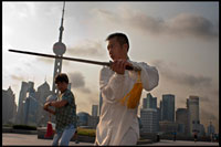 "CHINA: Shanghai, morning tai chi exercise on The Bund. Shanghi Bund : Early morning tai chi exercises with swords on the Bund in Shanghai China. The best taichi lessons I've had were from an old guy who practiced outside at 7am every morning. I learned 4 excellent techniques that I still use in my MMA training on a regular basis- a method of catching a kick and throwing your opponent, redirecting a straight punch and countering in the same motion, countering double underhooks with a throw, and escaping a shoulder lock while setting up your own.  It's a really fascinating martial art because every one of those dance like movements represents a simple practical fighting technique or strategy, but it's hard to see how the movements translate into combat applications without a master of the art demonstrating it. But either way even without a kungfu master, the forms themselves are great low impact exercise that you can find everywhere in the city for free every morning.   Most of the old folks in the parks won't mind if you tag along, just show up early and make sure to ask first if it's okay to join them.  The Bund (which means the ""Embankment"") refers to Shanghai's famous waterfront running along the west shore of the Huangpu River, forming the eastern boundary of old downtown Shanghai. Once a muddy towpath for boats along the river, the Bund was where the foreign powers that entered Shanghai after the Opium War of 1842 erected their distinct Western-style banks and trading houses. From here, Shanghai grew into Asia's leading city in the 1920s and 1930s, a cosmopolitan and thriving commercial and financial center. Many of the awesome colonial structures you see today date from that prosperous time and have become an indelible part of Shanghai's cityscape. After 1949, the street came to symbolize Western dominance over China and was shuttered."